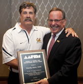 Tim Dutra, DPM (left) accepts Robert Barnes Distinguished Service Award from AAPSM Past President David Davidson, DPM