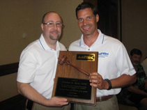 Dr. Bruce Williams presents outgoing President Dr. Matt Werd with the AAPSM Presidential Plaque in Hawaii