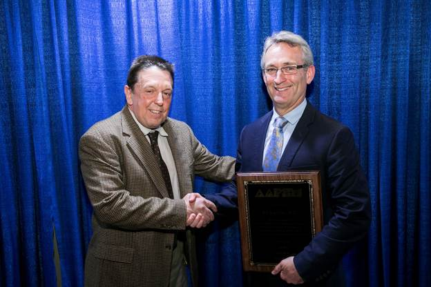 AAPSM President Alex Kor, DPM (l) congratulates AAPSM Excellence in Athletic Training Award recipient Edward Lacerte at the NATA meeting in Baltimore Friday afternoon
